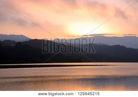 Beautiful landscape of reservoir at sunset with colorful sky reflections and wind power stations on the top of mountains.