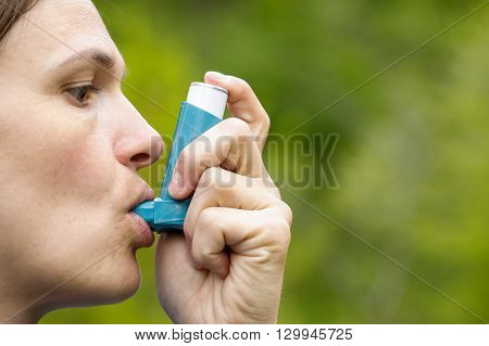Asthma patient inhaling medication for treating shortness of breath and wheezing. Chronic disease control allergy induced asthma remedy and chronic pulmonary disease concept.