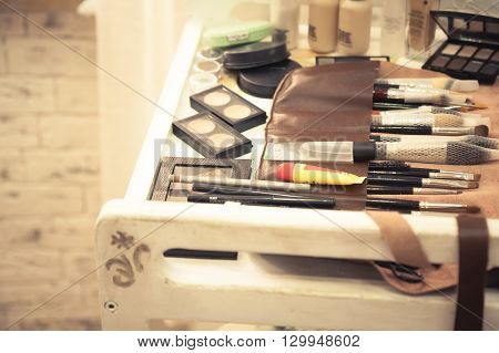 Table with makeup tools and cosmetics in beauty salon in vintage style