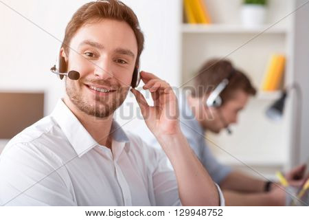 Ready to work with clients. Cheerful handsome bearded smiling man  using headset with micro and working in the call center while his colleague sitting at the table in the background