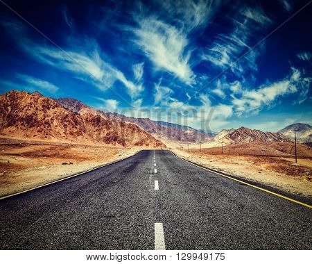 Vintage retro effect filtered hipster style image of road in mountains Himalayas and dramatic clouds on blue sky. Ladakh, Jammu and Kashmir, India