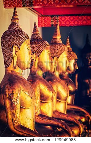 Travel Thailand Buddhism religion - vintage retro effect filtered hipster style image of sitting Buddha close up statues close up. Wat Pho temple, Bangkok, Thailand