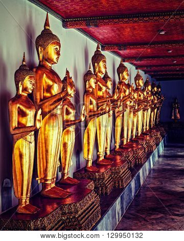 Travel Thailand Buddhism religion - vintage retro effect filtered hipster style image of standing golden Buddha statues.