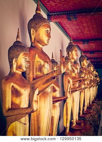 Travel Thailand Buddhism religion - vintage retro effect filtered hipster style image of standing golden Buddha statues close up.