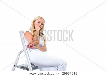 A beautiful young blond woman having a break from painting and siting on a ladder