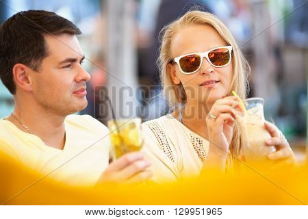 Young couple relaxing with refreshing drinks in long glasses on summer vacation with focus to an attractive woman wearing sunglasses