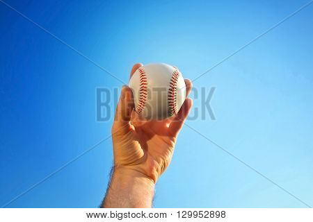 Baseball game. Baseball ball holding by hand against blue clean sky.