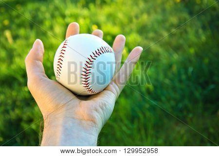 Baseball game. Baseball ball holding by hand against green fresh grass.