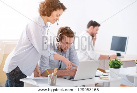 Concentrated on work. Pleasant positive smiling colleagues sitting working on the laptop and using headsets with micros while expressing gladness