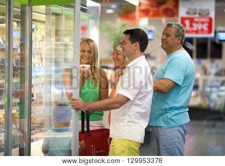 Family shopping together in a supermarket with the grandparents and parents of a young boy looking in a refrigerated cabinet
