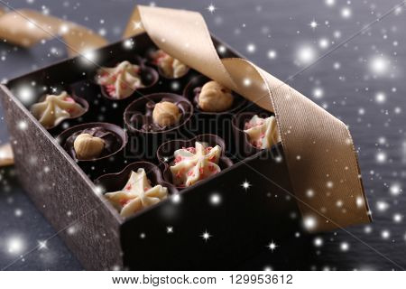 Chocolate sweets on wooden background with snow effect