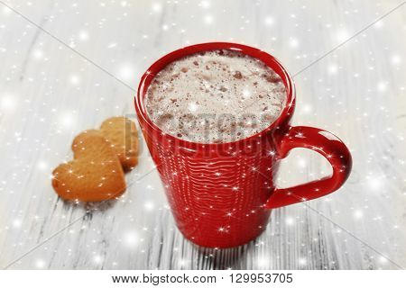 Red cup of hot cacao and heart shaped cookies on wooden background with snow effect