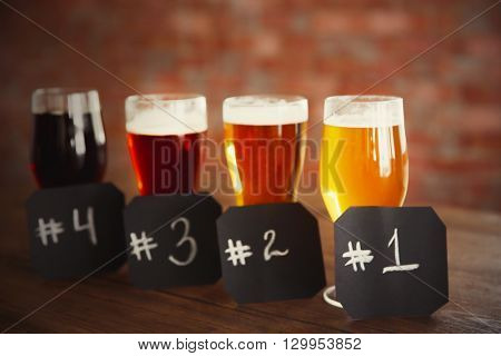 Glasses with different sorts of craft beer and numbering on wooden table. Retro blurred