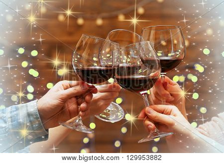 Clinking glasses of red wine in hands on bright lights background with snow effect