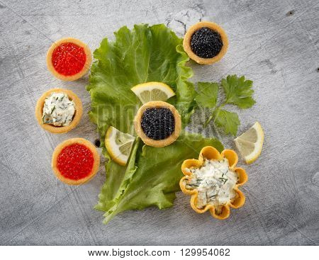 Tartlets filled with black caviar and cheese and dill salad on white plate and leaf against silver rustic wooden background horizontal top view