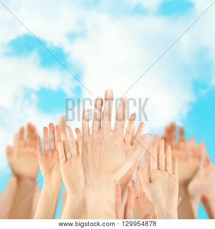 Crowd raising hands on blue sky background
