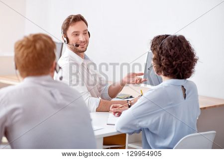Nice conversation, Cheerful delighted smiling colleagues sitting at the table and talking with each other while working with headset with micro