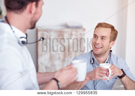 Lively talk, Cheerful delighted handsome smiling colleagues talking and drinking coffee while expressing positivity