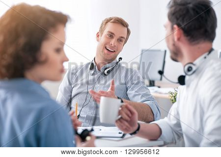 Exchange your ideas. Pleasant delighted positive colleagues sitting at the table and talking while woman working in the office