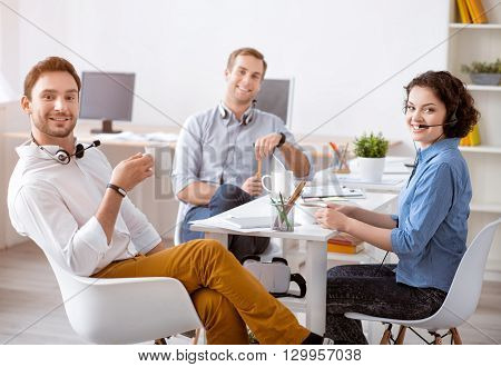 Work in concert. Cheerful content smiling colleagues sitting at the  table and having a break while drinking coffee