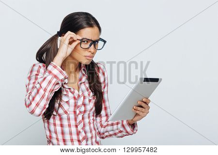 Beautiful geek woman holding digital tablet in studio on white