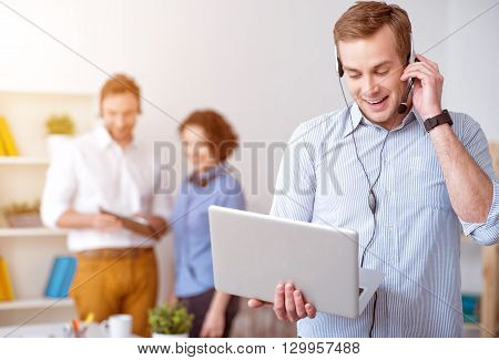 Set the connection. Pleasant delighted smiling man holding laptop and using headset with micro while his colleagues talking in the background