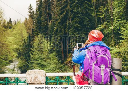 Young woman Traveler with a backpack taking a photo with smart phone mountain lake. Caucasus Abkhazia Lake Riza. Hiking Travel Lifestyle concept summer vacations outdoor.