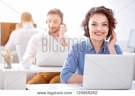 Nice worker.   Delighted  smiling beautiful woman using headset with micro  and sitting at the table while her colleagues working in the background