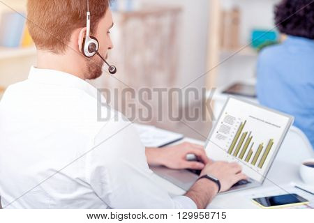 Concentrate on work. Pleasant serious professional man working on the laptop and using headset with micro while sitting at the table