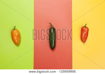 Three colored peppers. Yellow green and orange peppers on multi-color vivid backgrounds.