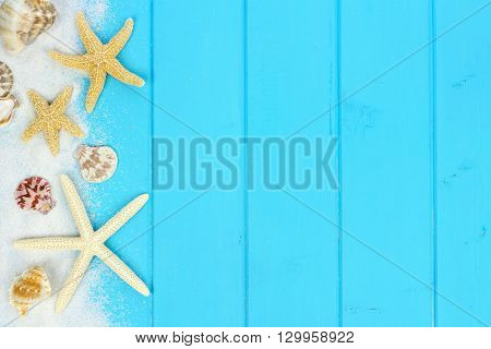Summer side border of sand sea shells and star fish on blue wooden background