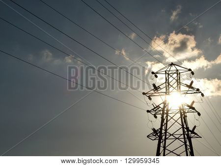 Backlit electricity power lines and pylon, uk