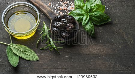Greek black olives, fresh green sage, rosemary, basil herbs, salt and oil on dark rustic wooden background.  Top view, copy space