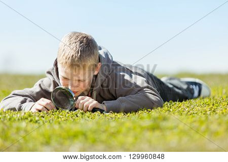 Boy Using Magnifying Glass Over Field Of Grass