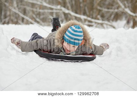 Little boy slides on soft sledges by snow in winter park.