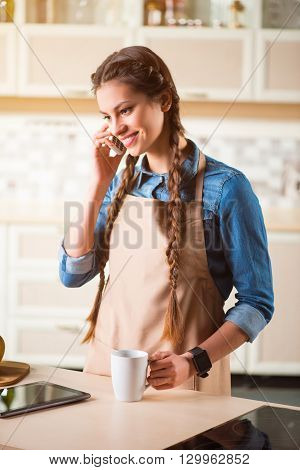 In touch with people. Pleasant cheerful beautiful smiling woman standing near the table and drinking coffee while talking on cell phone