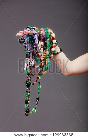 Closeup of woman hand palm holding many plentiful of precious jewelry necklaces beads. Fashion girl in studio on gray.