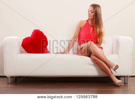Sad unhappy young woman girl with red heart shape pillow sitting on white sofa couch. Valentines day love.