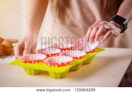 Almost done.   Pleasant woman holding cake pans while baking in the kitchen and standing near table