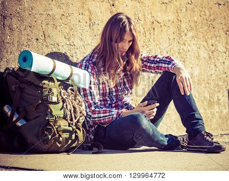 Man tourist backpacker outdoor sitting by grunge wall using mobile phone. Internet tourism. Young hipster guy tramping