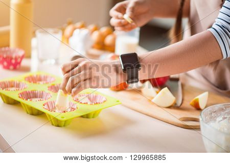 Make it delicious. Pleasant woman adding apples in the cake pans and baking while standing near the table