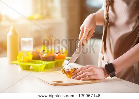 Share with people. Pleasant woman holding knife and cutting cake while standing in the kitchen