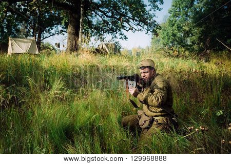 Teryuha, Belarus - October 4, 2015: Unidentified re-enactor dressed as World War II Soviet russian soldier with submachine gun sit in grass in forest