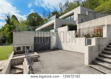 backyard of a concrete building with garage