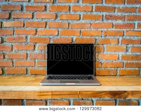Computer (Labtop) on Wooden Desk with Disordered Brick Wall Background