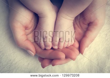 Newborn baby feet in mother's hands. Concept of child care, feeling safe, protect. Vintage