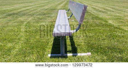 Metal childrens sports bench on a grass baseball or soccer field
