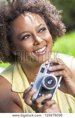Beautiful mixed race African American girl young woman with perfect teeth taking pictures or photographs outside with a retro digital camera