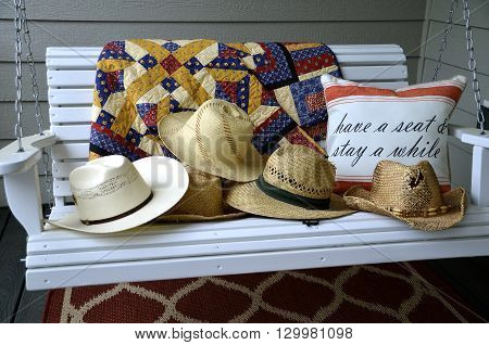 Vintage straw hats are left on an outdoor porch swing