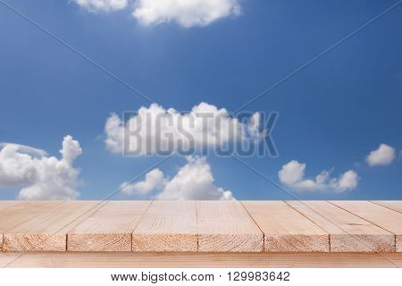 brown wood table top on bokeh abstract blue sky background - can be used for montage or display your products